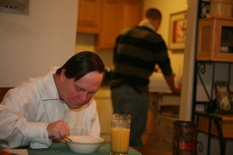 Ray eats a quick bowl of cereal as a staff member keeps the day flowing.