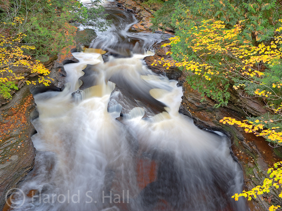 The falls and Rapids of the Presque Isle River in Michigan have carved our deep holes in the rocks, often called potholes, crating a beautiful fall scene.