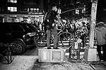 NEW YORK, NY — SEPTEMBER 24, 2020:  A person with a bike standing on a turned over new bin watches demonstrators protest against a Kentucky Grand Jury decision to not directly indict the officers involved in the shooting of Breonna Taylor, a 26 year-old EMT who was killed in her Louisville home by police on March 13th of this year, on September 24, 2020 in New York City.  Former police detective Brett Hankison faces three felony charges of wanton endangerment.  Photograph by Michael Nagle