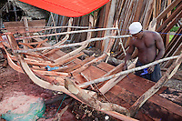 Nungwi, Zanzibar, Tanzania.  Dhow Construction.  Fitting the outer planks under the ribs that provide internal support and shape the hull.