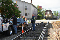 Tow truck operator Troy Harmon (center) looks on as Ryan Wardow, owner of Roadside Services Towing, secures a car to a tow truck, Monday, May 3, 2021 near the train tracks on Walnut Street and South Arkansas Street in Rogers. Rogers Police received a call at 9:29 am on Monday for a single car collision with a train. One person was admitted to the hospital, but his condition is unknown. Check out nwaonline.com/210504Daily/ for today's photo gallery. <br /> (NWA Democrat-Gazette/Charlie Kaijo)