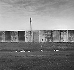 Scan of vintage print. Topographic landscape of metal fence hiding drive-in theatre. 1977. Negative file #77-288-#4