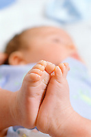 Close up of a newborn's feet with toes curled