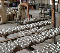 Chinese workers lift clay cups at a porcelain workshop in Jingdezhen, Jiangxi Province, China. The township of Jingdezhen is well known in China as the country's porcelain capital ever since it was selected exactly one thousand years ago as the royal porcelain provider for the imperial court..24-JUN-04
