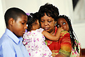 Ashaun Cotton, Debera Jefferson, holding her granddaughter, and  her other granddaughter Destiny Patterson listen during church service in New Orleans, Sun., Aug. 27, 2006.<br />(Cheryl Gerber for USA Today)