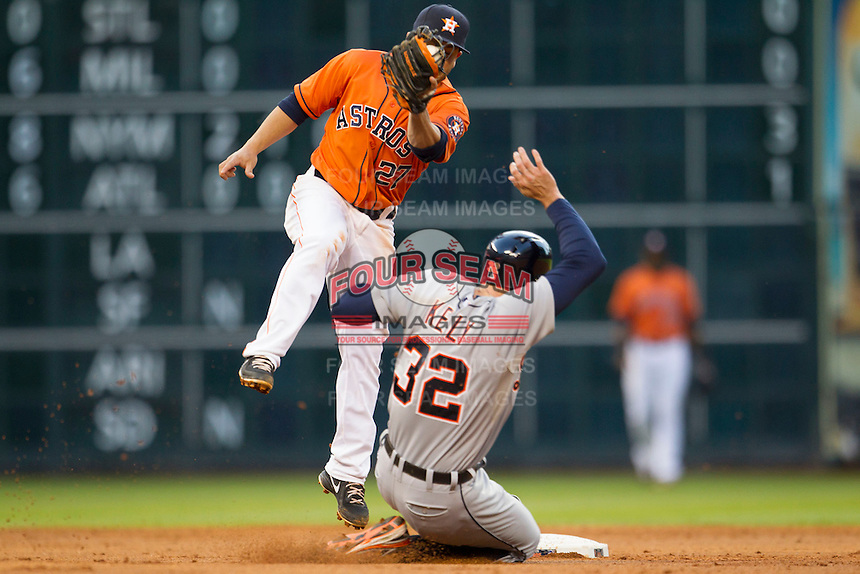 Houston Astros second baseman Jose Altuve (27) attempts to tag Detroit Tigers baserunner Don Kelly (32) during a steal attempt in the MLB baseball game on May 3, 2013 at Minute Maid Park in Houston, Texas. Detroit defeated Houston 4-3. (Andrew Woolley/Four Seam Images).