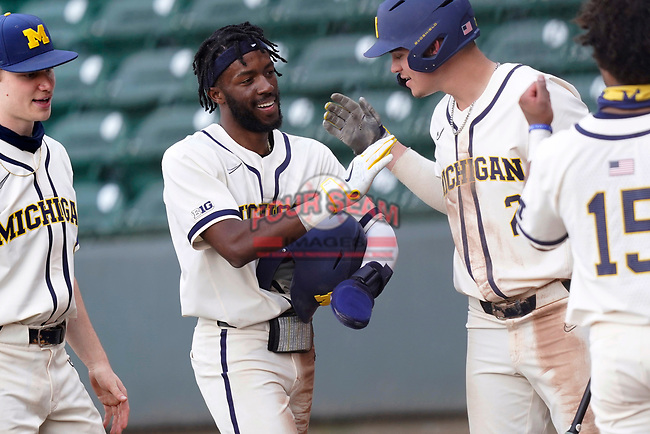 Center fielder Christian Bullock (5) of the Michigan Wolverines is greeted after scoring a run in a game against the Purdue Boilermakers on Friday, March 12, 2021, at Fluor Field at the West End in Greenville, South Carolina. (Tom Priddy/Four Seam Images)
