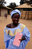 The Gambia. Woman wearing bright clean blue traditional cotton dress matching headscarf holding her maternity medical record card.
