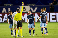 CARSON, CA - OCTOBER 18: Referee Victor Rivas shows Russell Teibert #31 of the Vancouver Whitecaps a yellow card during a game between Vancouver Whitecaps and Los Angeles Galaxy at Dignity Heath Sports Park on October 18, 2020 in Carson, California.