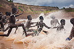 Young boys run into the Omo River, Ethiopia