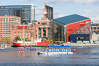 Tourists enjoy paddle boats near the Baltimore National Aquarium and Lightship Chesapeake as a Water Taxi approaches the Harborplace landing in the Inner Harbor of Baltimore, Maryland.
