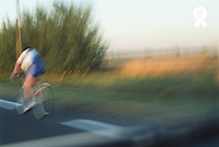 Cyclist on road, rear view (blurred motion) (Licence this image exclusively with Getty: http://www.gettyimages.com/detail/200387433-001 )