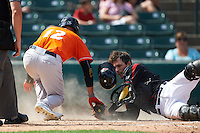 Norfolk Tides designated hitter Dariel Alvarez (12) after being tagged out by catcher John Ryan Murphy (12) on a play at the plate during a game against the Rochester Red Wings on July 17, 2016 at Frontier Field in Rochester, New York.  Rochester defeated Norfolk 3-2.  (Mike Janes/Four Seam Images)