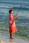 A local i-kiribati fishing from the beach on the island of Kiritimati in Kiribati