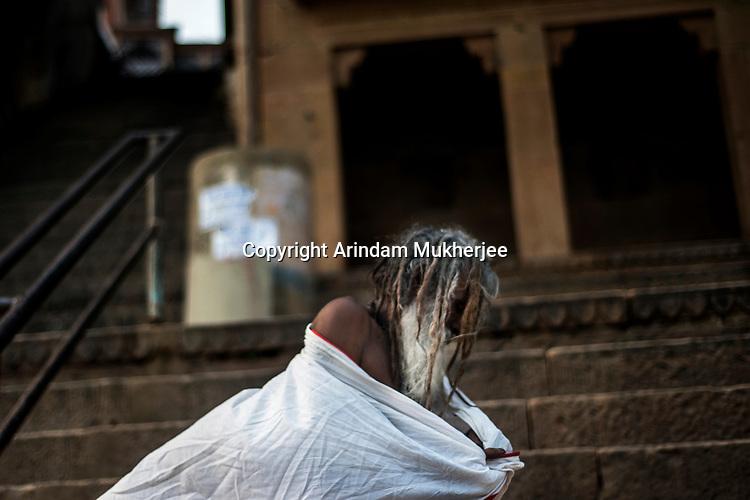 A holy man changes cloth after taking bath at a ghat in Varanasi, Uttar Pradesh, India.