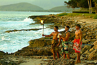 At Paradise Cove Luau, three Hawaiian kane (men) on the rocky shore at Ko Olina look out to sea at sunset. One holds a torch, another a conch shell - used for communication in early Hawaii. Image also available in vertical format.