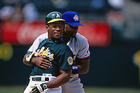 OAKLAND, CA - Rickey Henderson of the Oakland Athletics jokes around with Carlos Delgado of the Toronto Blue Jays at the Oakland Coliseum in Oakland, California on August 18, 1998. (Photo by Brad Mangin)