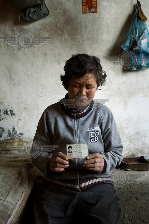 61-year-old Wang Xiu Qin holds up a photograph of her son, Chen Guo Qi. Her son has been in jail for over a decade waiting for his death sentence to be carried out following a confession that he made while under torture. Mrs. Wang believes that the court proceedings and evidence surrounding the case to be suspect and has been petitioning for an investigation into her son's conviction.
