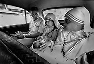 """Calcutta, India. April 04, 1975. On her morning taxi drive, Mother Teresa is handed a newborn infant through the car window at a stop by an unknown person. This happens to her almost daily. Mother Teresa (Agnes Gonxha Boyaxihu) the Roman Catholic, Albanian nun revered as India's """"Saint of the Slums,"""" was awarded the 1979 Nobel Peace Prize."""