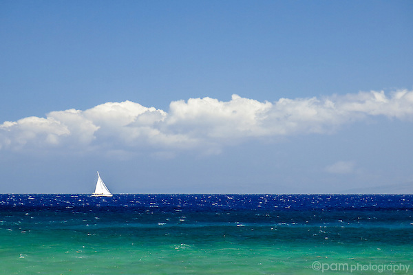 White sailboat on blue Pacific ocean off the coast of Maui