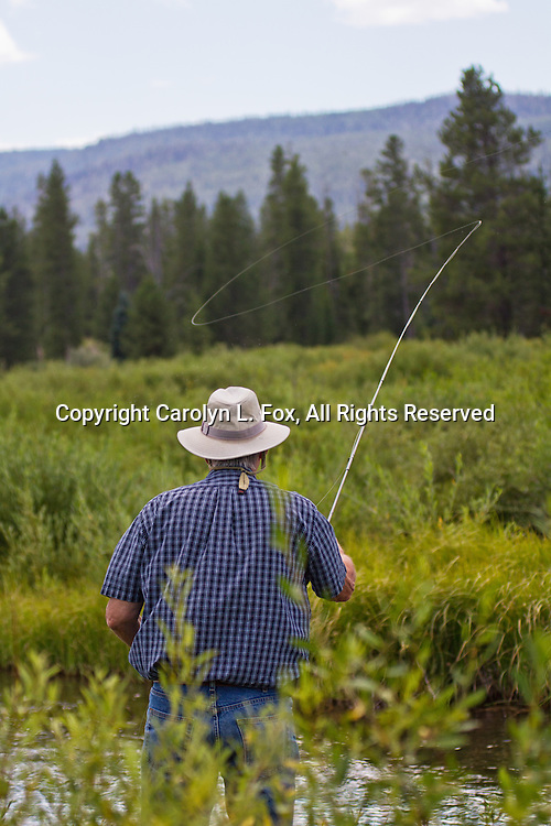 A man is fly fishing on a river in Montana.