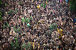 "People jam the grounds of the Catholic church to hear Mass during the annual Taong Putik, or ""mud people,"" festival in Bibiclat, on Luzon island, Philippines. Despite sometimes heavy monsoon rains, the festival draws hundreds of devotees every year. The event honors St. John the Baptist, and devotees cover themselves in mud, banana leaves and vines to symbolize the animal skins he wore in the Bible. June 24, 2011."