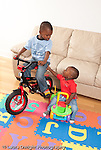 12 month old baby boy on wheeled plastic toy looking at his 3 year old brother on his bicycle with training wheels vertical