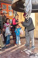 Bodhnath, Nepal.  Ringing Giant Bell to Celebrate Tibetan New Year.  Donations of Money on the Ground.