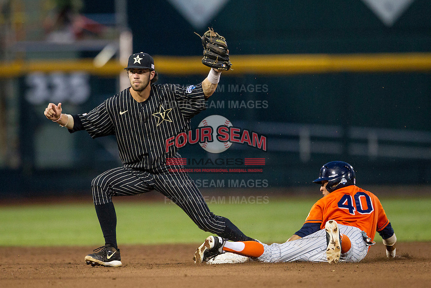 Vanderbilt Commodores shortstop Dansby Swanson (7) awaits call as Cal State Fullerton Titans baserunner Josh Vargas (40) slides past second base during the NCAA College baseball World Series on June 14, 2015 at TD Ameritrade Park in Omaha, Nebraska. The Titans were leading 3-0 in the bottom of the sixth inning when the game was suspended by rain. (Andrew Woolley/Four Seam Images)