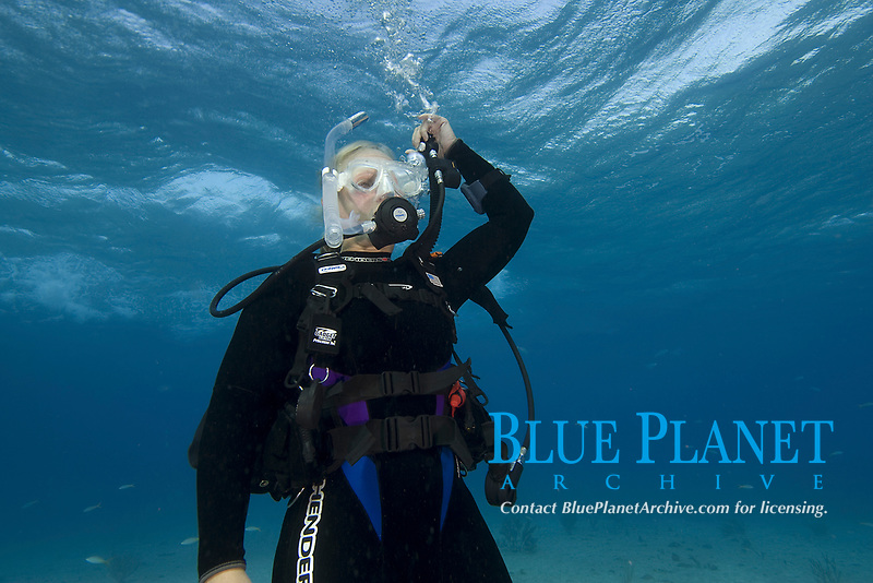 Scuba diver emptying air from buoyancy compensator (BC) to descend.
