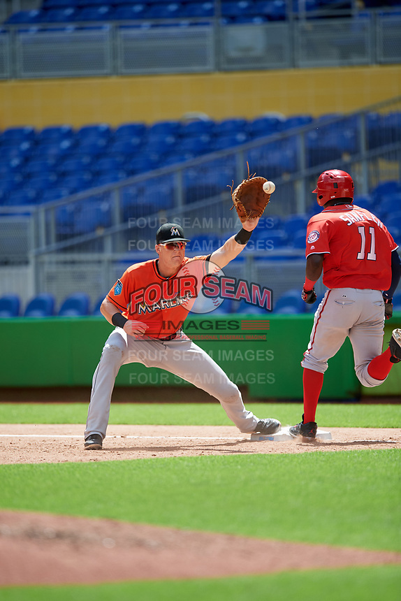 Miami Marlins Sean Reynolds (47) waits to receive a throw as Caldioli Sanfler (11) beats out the throw during a Florida Instructional League game against the Washington Nationals on September 26, 2018 at the Marlins Park in Miami, Florida.  (Mike Janes/Four Seam Images)