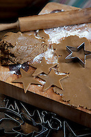 Detail of cookie dough cut into star shapes on a chopping board