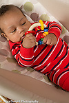 3 month old baby boy closeup holding toy with moving colorful wooden rings