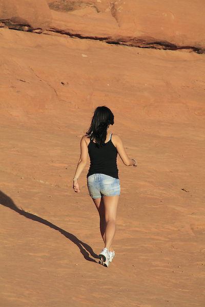 Woman walking on slickrock in Arches National Park, Moab, Utah, USA. .  John offers private photo tours in Arches National Park and throughout Utah and Colorado. Year-round.