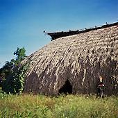 Pavuru Village, Brazil. Sting standing outside a large malloca; Xingu Indigenous reserve, Para & Goias State.