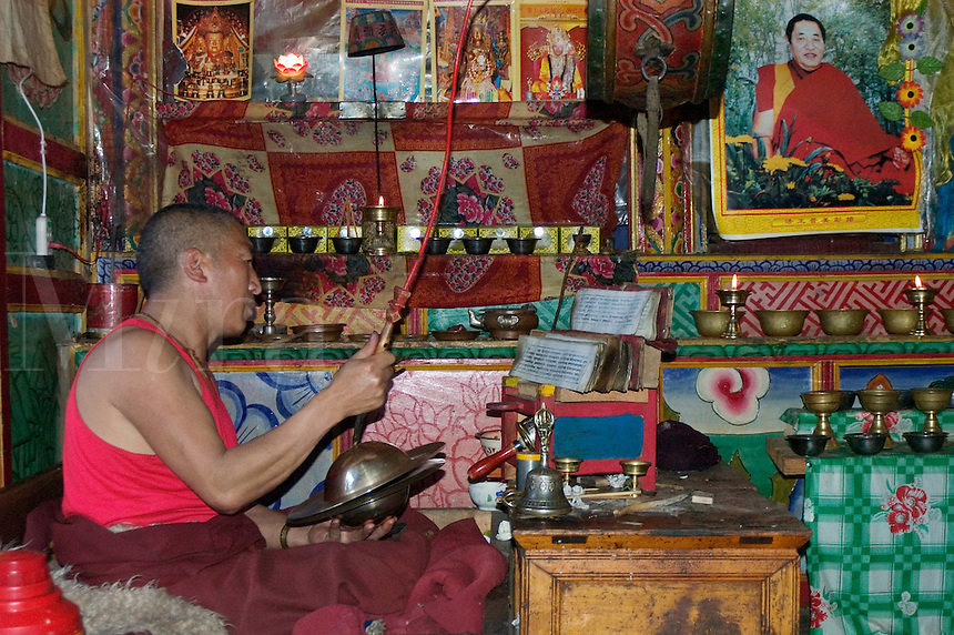 Monk plays instrument & recites text in a Tibetan Monastery in Dabpa County, Kham - Sichuan Province, China, (Tibet)