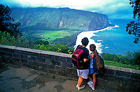 A couple gazes at lush Waipio Valley on the Big Island of Hawaii from a stone overlook.