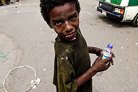 A Colombian street kid gets high by sniffing the shoe glue in the slum of Calvario, Cali, Colombia, 5 April 2004. Calvario, a slum right in the centre of the city, is considered the social bottom of Cali society. Poor dwellers recollect the garbage in the near city centre to sell it for recycling, while their children get high by sniffing the shoe glue on the dirty streets of ghetto. The order in Calvario is maintained by the illegal authorities, usually former policemen or army members, who set their own rules. Criminality, drug abuse, unemployment never allow the slum people jump off the misery and stop being the second category citizen within the rigid society of Colombia. Although Christian missionary organizations attempt to provide help, the overall situation does not improve.