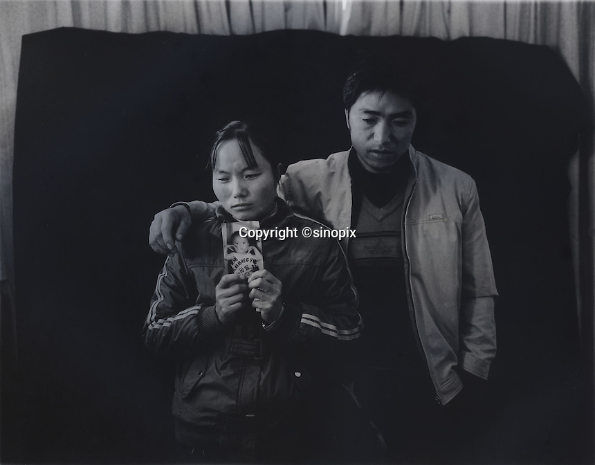 """Mr and Mrs Ma holds a picture of her son Ma Purei, 3 and half years old,  who was stolen  March 22nd  2004.  The message reads, """"Papa and Mama are hoping that you will come home soon.""""  Mrs Ha and Mrs Ma is one of thousands of migrant mothers whose children have been stolen and sold to rich families desperate for a boy. Families are limited to a single child under the China's ruthless One Child Policy."""
