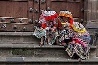 Peru, Cusco.  Young Quechua Women in traditional dress sitting on church steps.
