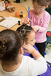 Education Preschool 4 year olds two girls styling hair of a girl, one using watercolor paint brush in dying operation