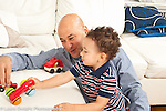 Toddler boy age 18 months at home playing with father and toy cars language development father talking and making car noises