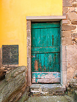 The old doors of Corniglia, Italy create a nice design and contrasting colors with the brightly colored buildings.