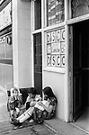 Children siblings brother and older sister look after family babies. Older girl playing with doll. They are waiting outside a Lunch Time Disco pub for their parents to re emerge. The Rising Sun, later changed to The Paper Moon, 24, Blackfriars Rd, SE1 London 1970s UK .
