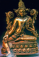 "India: Avalokitesvara--12th C. bronze, 10"" high. Chandra doesn't say who this divinity is. Figure sits on lotus pedestal, and between lotus plants.  A diadem--not visible- in form of Buddha. Note vertical third eye."
