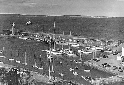 Dinghy Week 1950 at Dunmore East, with the rapidly-expanding IDRA 14 Class present in strength and lying to a line of moorings afloat, while the harbour is dominated by the sky-scraping mast of Aylmer Hall's 12 Metre Flica from Cork, and the picture is made complete with a Naval Service guardship