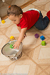 10 month old baby boy throwing wooden block into colander