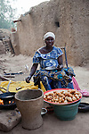 A woman in the pottery village of Kalabougou, Mali sells fari masas and ceceenas made of flour and beans.