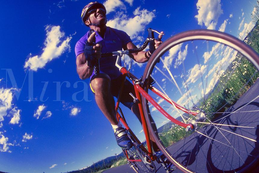 Man road biking on bike path in summer.