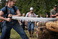 "The annual logging show held in Thorne Bay on Prince of Wales Island in the Tongass National Forest is the ""real thing"" --not a tourist show--where loggers, past loggers and wanna be loggers compete.  Men and women team up to cut through a hard spruce  log in a timed event called ""Jack and Jill."" They use the ""Misery whip,"" a two person bladed saw that takes muscles and skill to maneuver.There was a two person wheelbarrow race.  They also compete to empty a skiff full of water, toss hatchets at a target, throw chain saws, stack wood, and the big event is to climb a 65 foot pole..Cody Thomas, independent logger competes in many of the events."